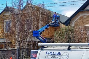 Plumber using cherry picker to access roof of house