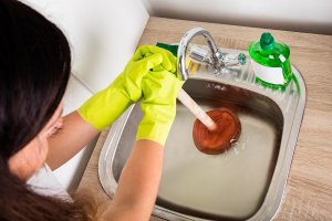Woman using a plunger to clear drain in a kitchen sink