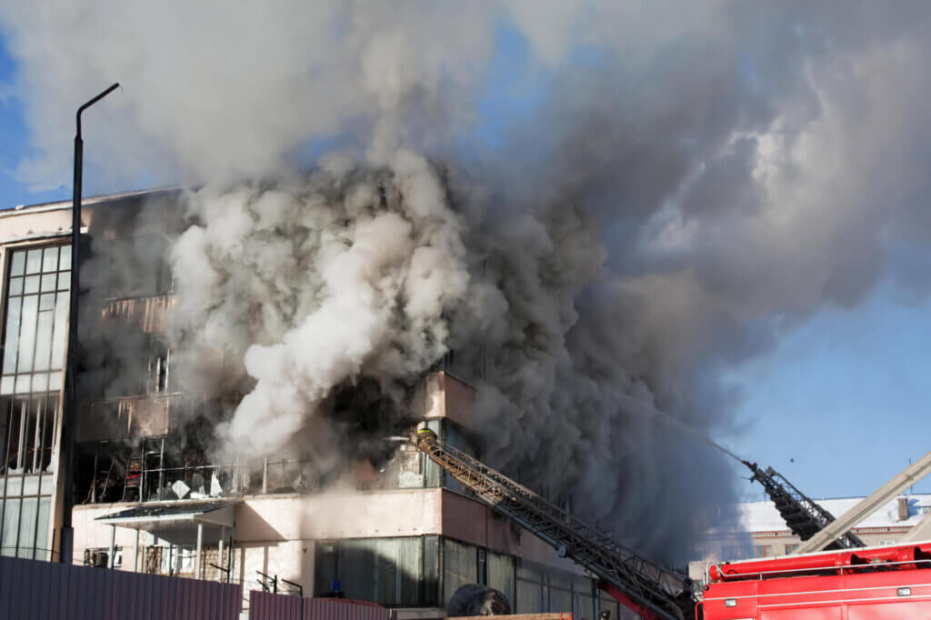 Firefighters working to fight a fire in a building consumed in smoke with heat and visibility beyond tenable levels for a safe escape